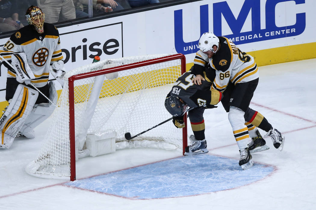 Vegas Golden Knights left wing David Perron (57), center, is pushed down by Boston Bruins defenseman Kevan Miller (86), right, during the third period of an NHL hockey game at T-Mobile Arena in La ...