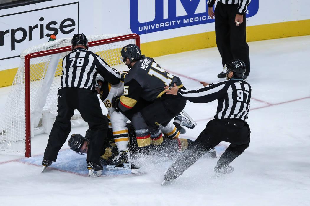 Vegas Golden Knights left wing David Perron (57), center, is pushed down by Boston Bruins defenseman Kevan Miller (86), center, as Vegas Golden Knights defenseman Jon Merrill (15), right, interven ...