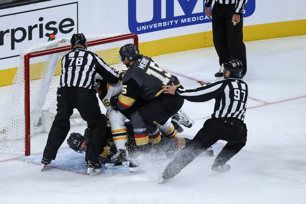 Vegas Golden Knights left wing David Perron (57), center, is pushed down by Boston Bruins defenseman Kevan Miller (86), center, as Vegas Golden Knights defenseman Jon Merrill (15), right, interven ...