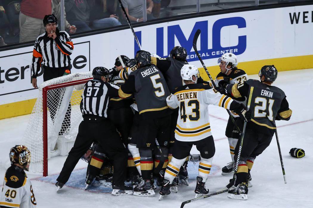 Vegas Golden Knights and the Boston Bruins break up a fight during the third period of an NHL hockey game at T-Mobile Arena in Las Vegas, Sunday, Oct. 15, 2017. Vegas Golden Knights won 3-1. Joel  ...