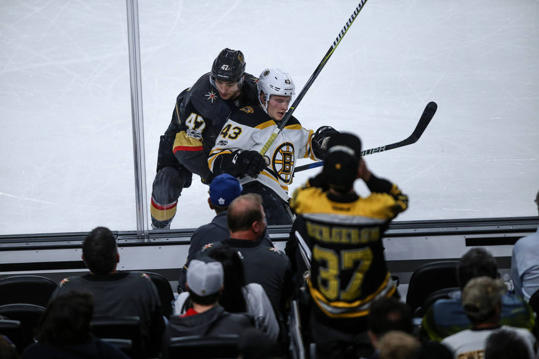 Vegas Golden Knights defenseman Luca Sbisa (47), left, and Boston Bruins center Danton Heinen (43), right, chase after the puck during the third period of an NHL hockey game at T-Mobile Arena in L ...