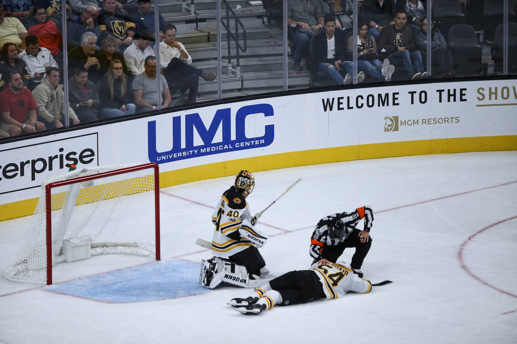 Boston Bruins defenseman Adam McQuaid (54), center, lies on the ground after being injured during the third period of an NHL hockey game against the Vegas Golden Knights at T-Mobile Arena in Las V ...