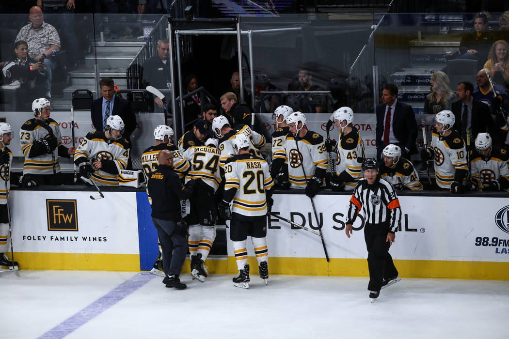Boston Bruins defenseman Adam McQuaid (54), center, is walked off the ice rink after being injured during the third period of an NHL hockey game against the Vegas Golden Knights at T-Mobile Arena  ...