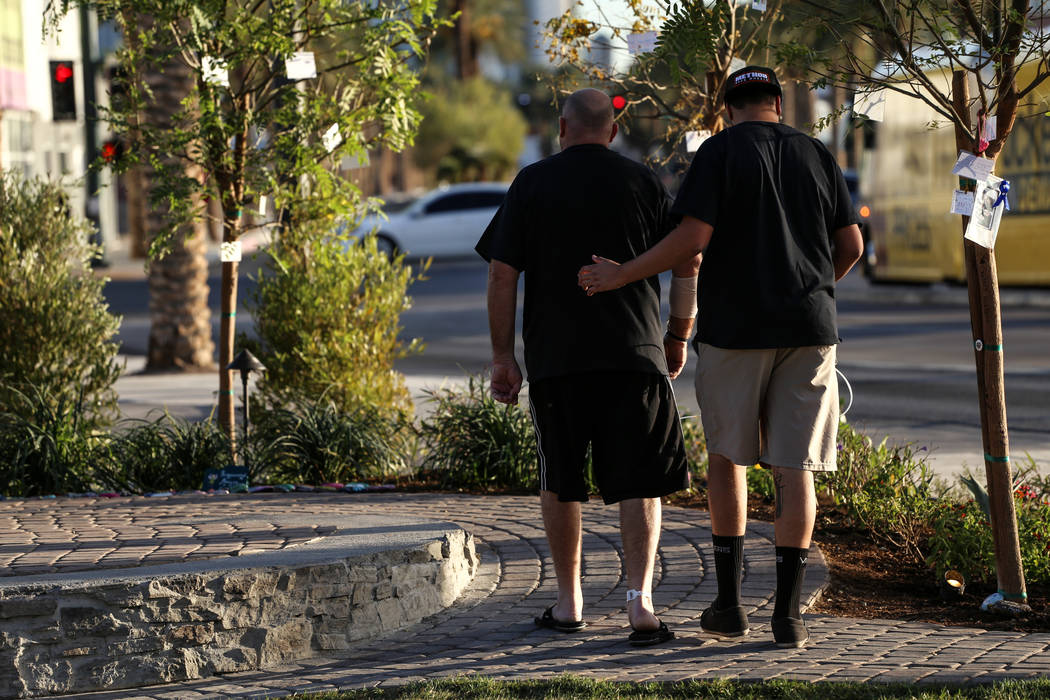 A man that was shot multiple times during the Route 91 Harvest Festival mass shooting, left, walks around a memorial at the Las Vegas Community Healing Garden after being discharged from the hospi ...