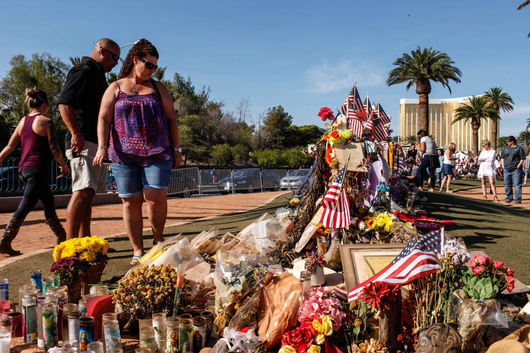 Jeff Regino, 40, left, and Melissa Regino, 40, right, both of Sacramento visit a memorial at the Welcome to Fabulous Las Vegas sign in Las Vegas, Monday, Oct. 16, 2017, honoring the victims of the ...