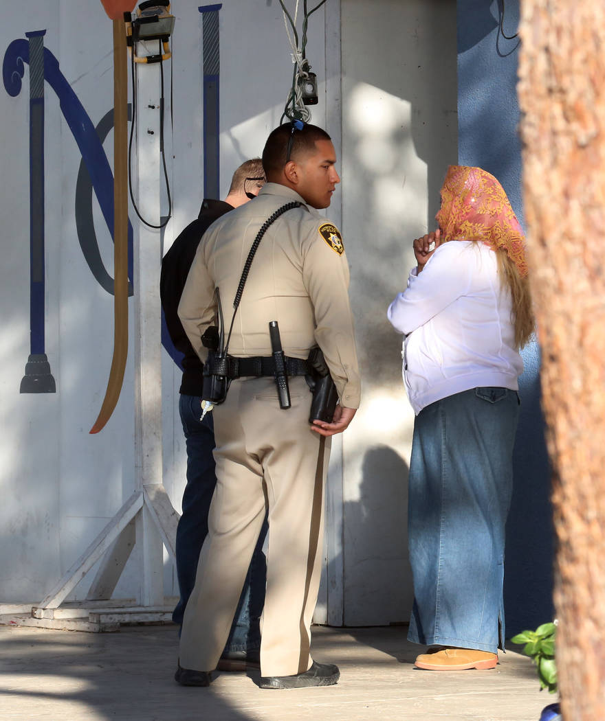 Las Vegas police officers talk to a church goer outside Iglesia La Luz Del Mundo after a man suffering gunshot wounds to his head and shoulder was found at Cedar Street Monday, Oct. 16, 2017, in L ...