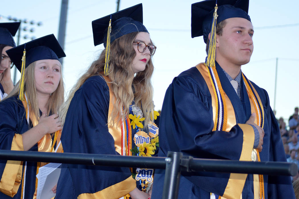 Salutatorian Alea Lehr, left, and valedictorians Mira Newby center, and Michael Martinelli listen to the national anthem during Boulder City High School's graduation ceremony on Friday evening at  ...