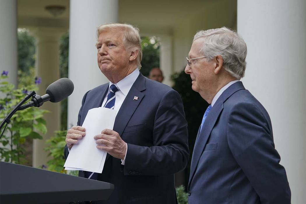 President Donald Trump picks up his notes after he and Senate Majority Leader Mitch McConnell of Ky., finish up speaking to members of the media in the Rose Garden of the White House, Monday, Oct. ...