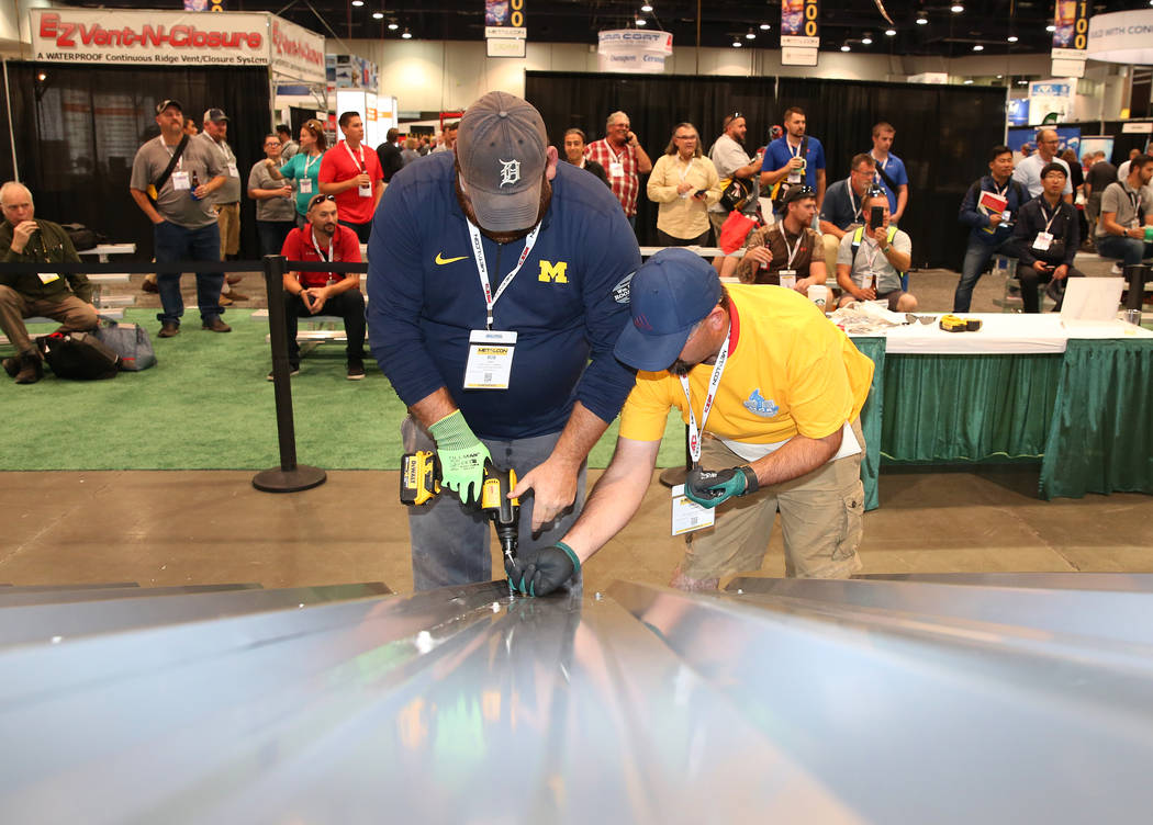 Bob Faint, left, and David Austin participate in Screw Gun Challenge during the 2017 MetalCon Expo at the Las Vegas Convention Center Wednesday, Oct. 18, 2017. Contestants install a series of self ...