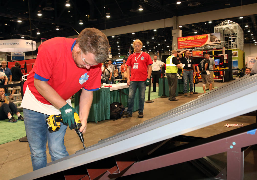Marc Vlietstra participates in Screw Gun Challenge as his brother Seth, right, looks on during the 2017 MetalCon Expo at the Las Vegas Convention Center Wednesday, Oct. 18, 2017. Contestants insta ...