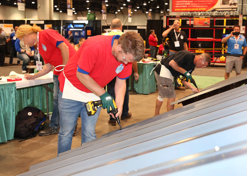 Marc Vlietstra, center, participates in Screw Gun Challenge during the 2017 MetalCon Expo at the Las Vegas Convention Center Wednesday, Oct. 18, 2017. Contestants install a series of self-drilling ...
