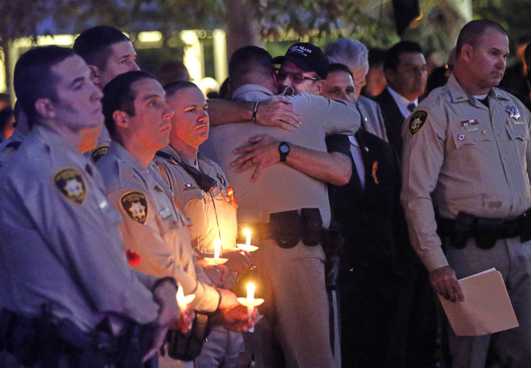Las Vegas police officers embrace during a candlelight vigil for officer Charleston Hartfield, who was killed while off-duty in a mass shooting, at Police Memorial Park in Las Vegas on Thursday, O ...