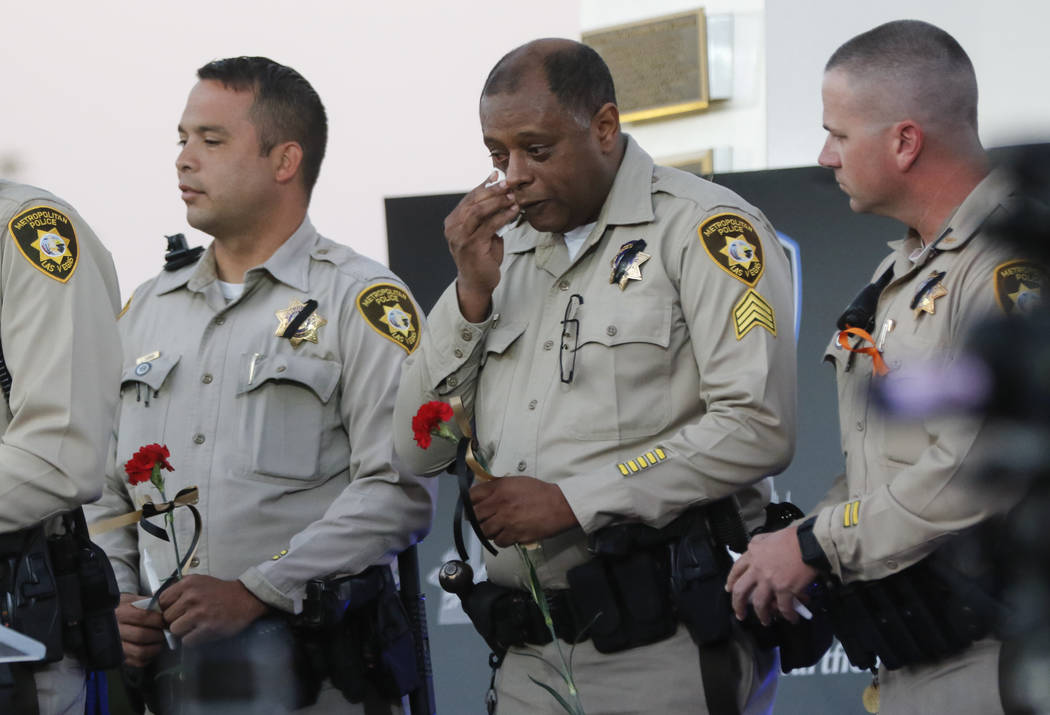 Las Vegas police officers react during a candlelight vigil for Las Vegas police officer Charleston Hartfield, who was killed while off-duty in a mass shooting, at Police Memorial Park in Las Vegas ...