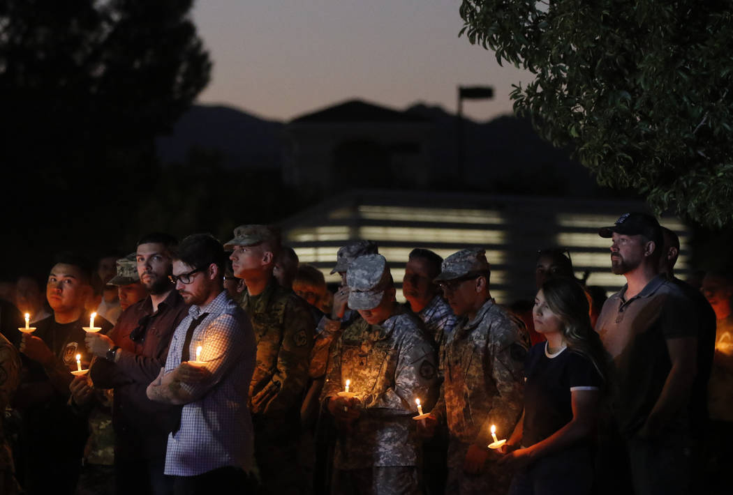 People attend a candlelight vigil for Las Vegas police officer Charleston Hartfield, who was killed while off-duty in a mass shooting, at Police Memorial Park in Las Vegas on Thursday, Oct. 5, 201 ...