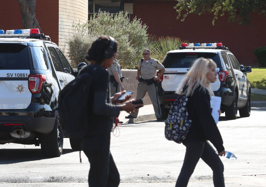 Students at Clark High School walk past Las Vegas police officers Monday, Oct. 16, 2017. A 16-year-old student was taken to University Medical Center after she was stabbed by another 14-year-old f ...
