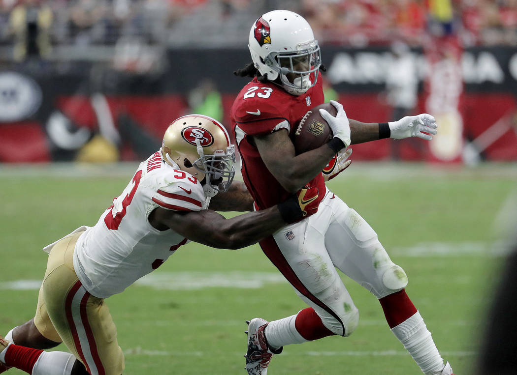 Arizona Cardinals running back Chris Johnson (23) tries to elude San Francisco 49ers middle linebacker NaVorro Bowman (53) during the second half of an NFL football game, Sunday, Oct. 1, 2017, in  ...
