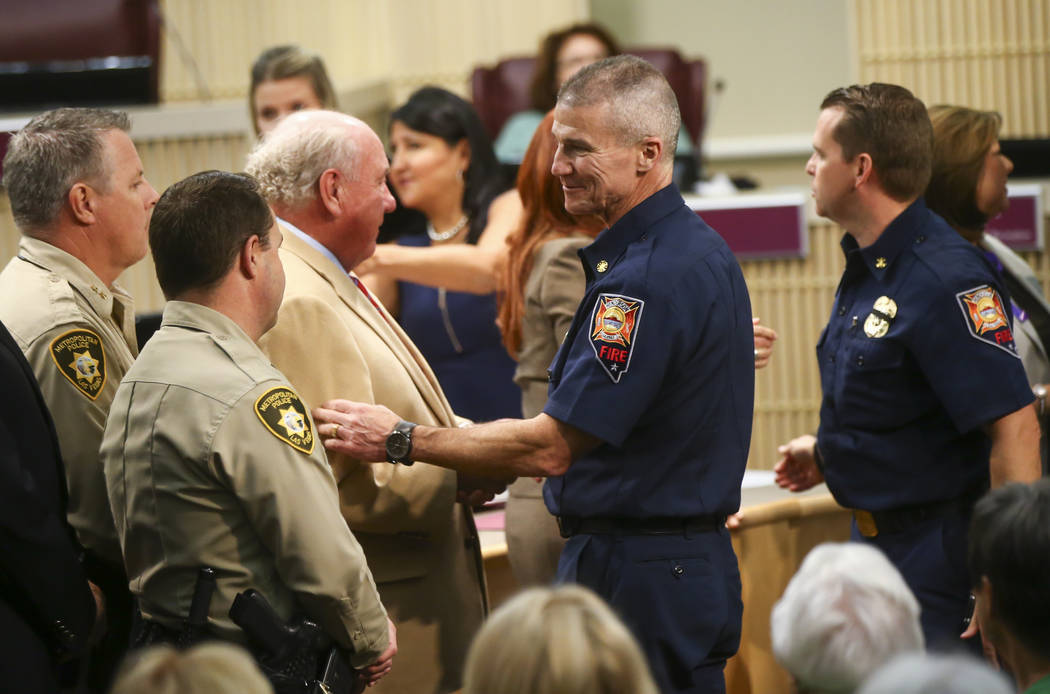 Henderson Fire Department Chief Shawn White, center right, is greeted by Henderson City Councilman Dan Shaw as first responders in the Oct. 1 shooting are recognized during a Henderson City Counci ...