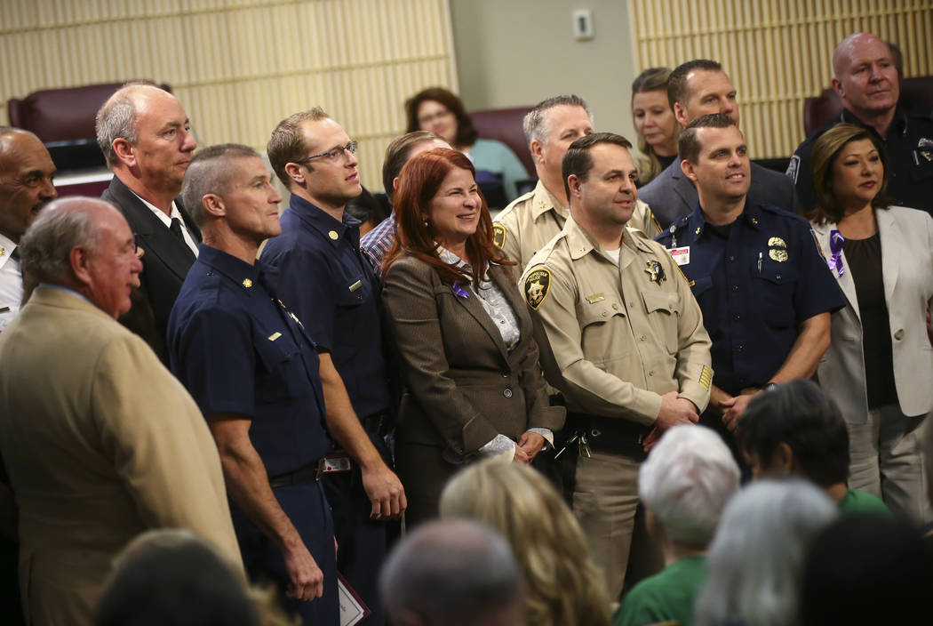 Henderson Mayor Debra March, center, poses for a photo with first responders in the Oct. 1 shooting as they are recognized during a Henderson City Council meeting on Tuesday, Oct. 17, 2017. Chase  ...