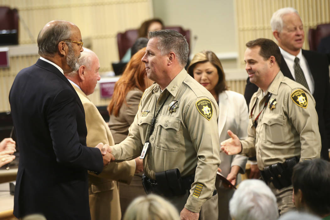 Metropolitan Police Department Assistant Sheriff Todd Fasulo, center, greets Henderson City Councilman John Marz as first responders in the Oct. 1 shooting are recognized during a Henderson City C ...