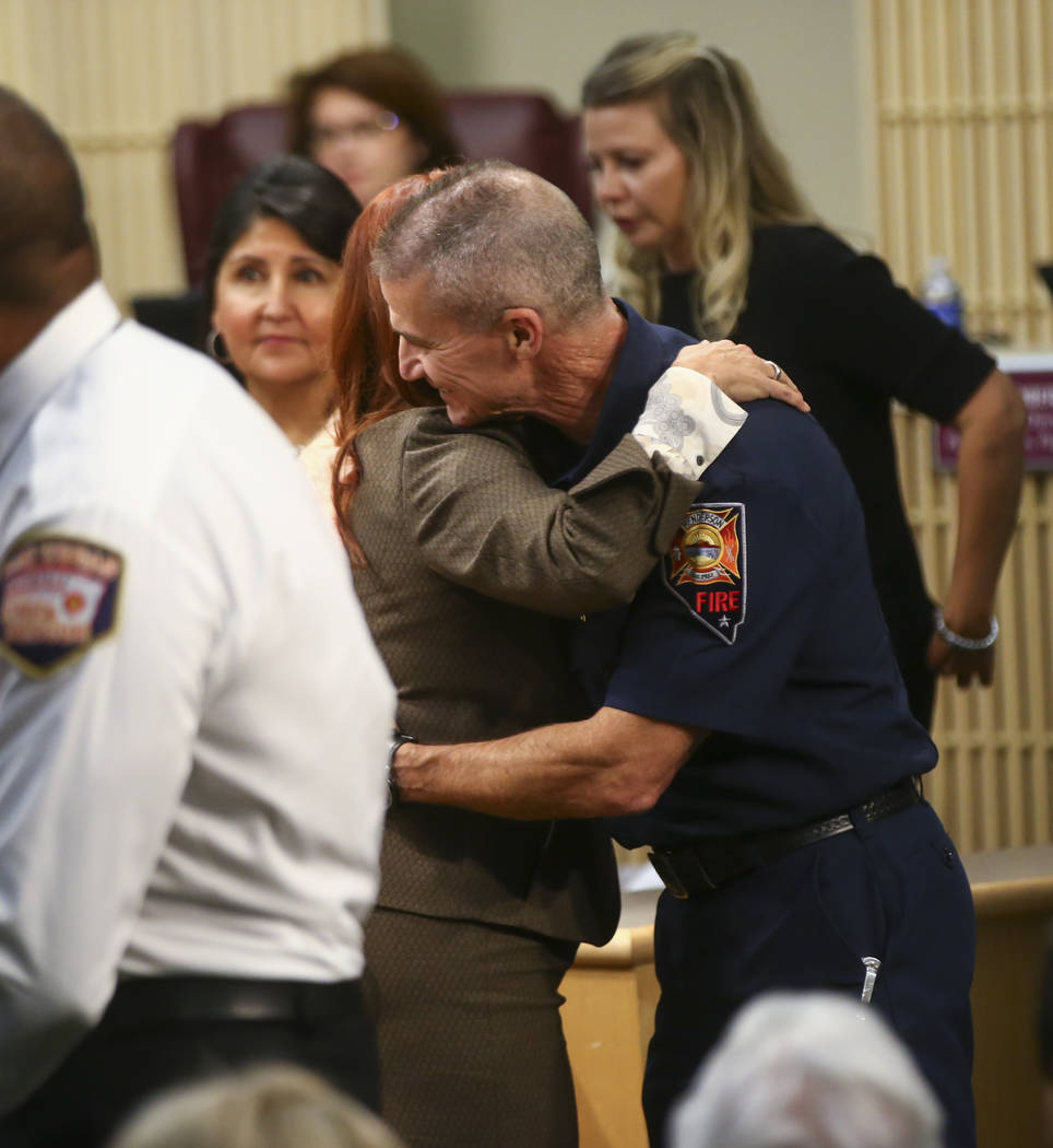 Henderson Fire Department Chief Shawn White, right, is embraced by Henderson Mayor Debra March as first responders in the Oct. 1 shooting are recognized during a Henderson City Council meeting on  ...