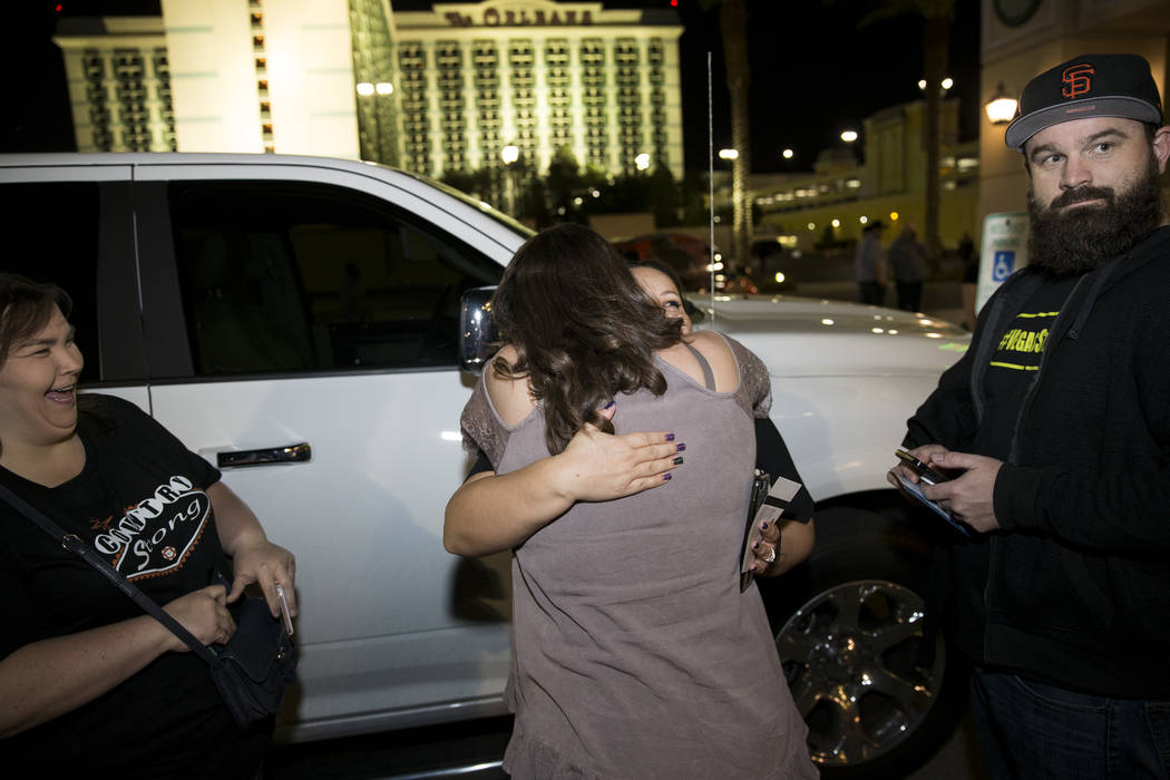 Anna Kopp, front center, embraces her friend Amber Diskin, before the Vegas Strong benefit concert, at the Orleans Arena in Las Vegas, Thursday, Oct. 19, 2017. Michele Langlois and Diskin's husban ...