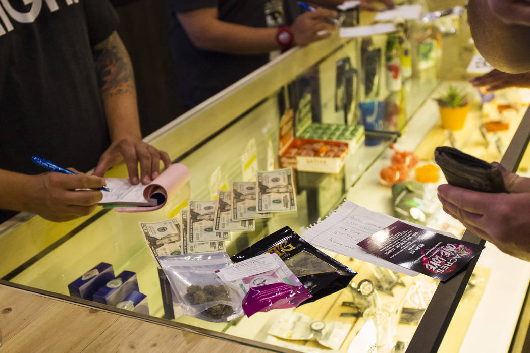 Henderson resident Ethan, right, purchases marijuana products during the first day of recreational sales at Acres Cannabis in Las Vegas on Saturday, July 1, 2017. Chase Stevens Las Vegas Review-Jo ...