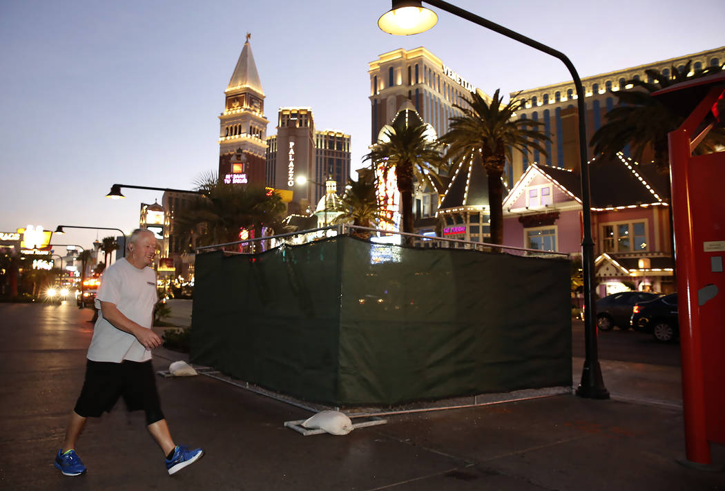 A pedestrian walks past the Strip bollards project site Tuesday, Oct. 17, 2017, in front of the Mirage hotel-casino. The steel bollards project will be completed without impacting pedestrian or ve ...