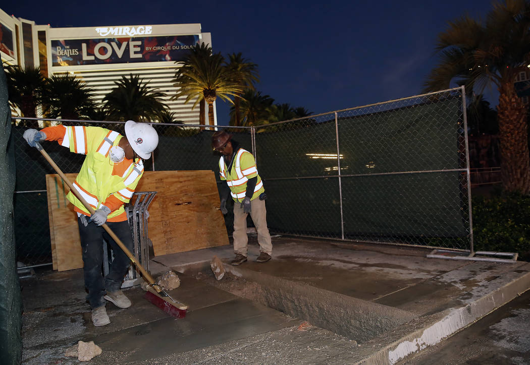 Project workers dig under the sidewalk at the Strip bollards project site, to locate underground utilities, Tuesday, Oct. 17, 2017, in front of the Mirage hotel-casino. The steel bollards project  ...