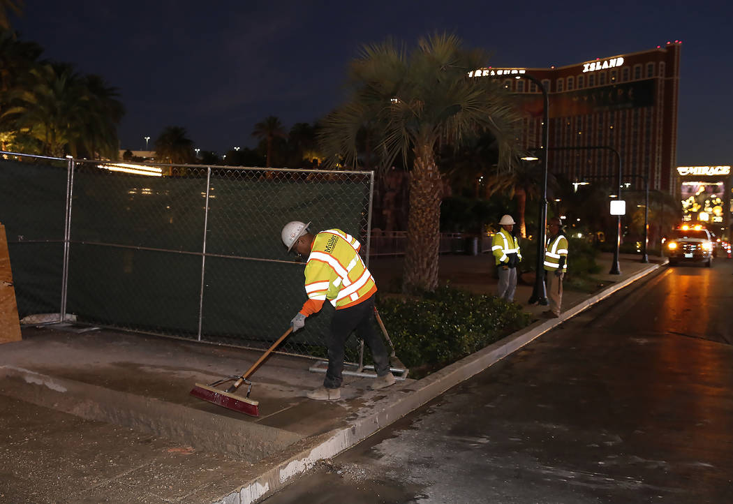A project worker sweeps the sidewalk at the Strip bollards project site Tuesday, Oct. 17, 2017, in front of the Mirage hotel-casino. The steel bollards project will be completed without impacting  ...