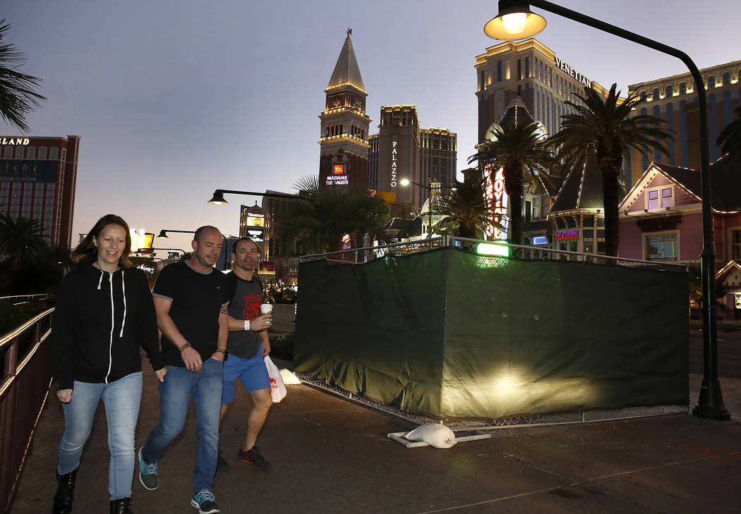 Pedestrians walk past the Strip bollards project site Tuesday, Oct. 17, 2017, in front of the Mirage hotel-casino. The steel bollards project will be completed without impacting pedestrian or vehi ...