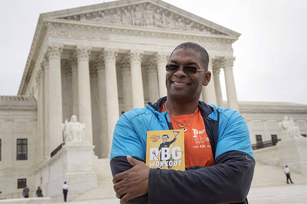 "In this Oct. 13, 2017, photo, Bryant Johnson, personal trainer for Supreme Court Justice Ruth Bader Ginsburg poses in Washington, with his new book, ""The RBG Workout: How She Stays Strong ... and  ..."