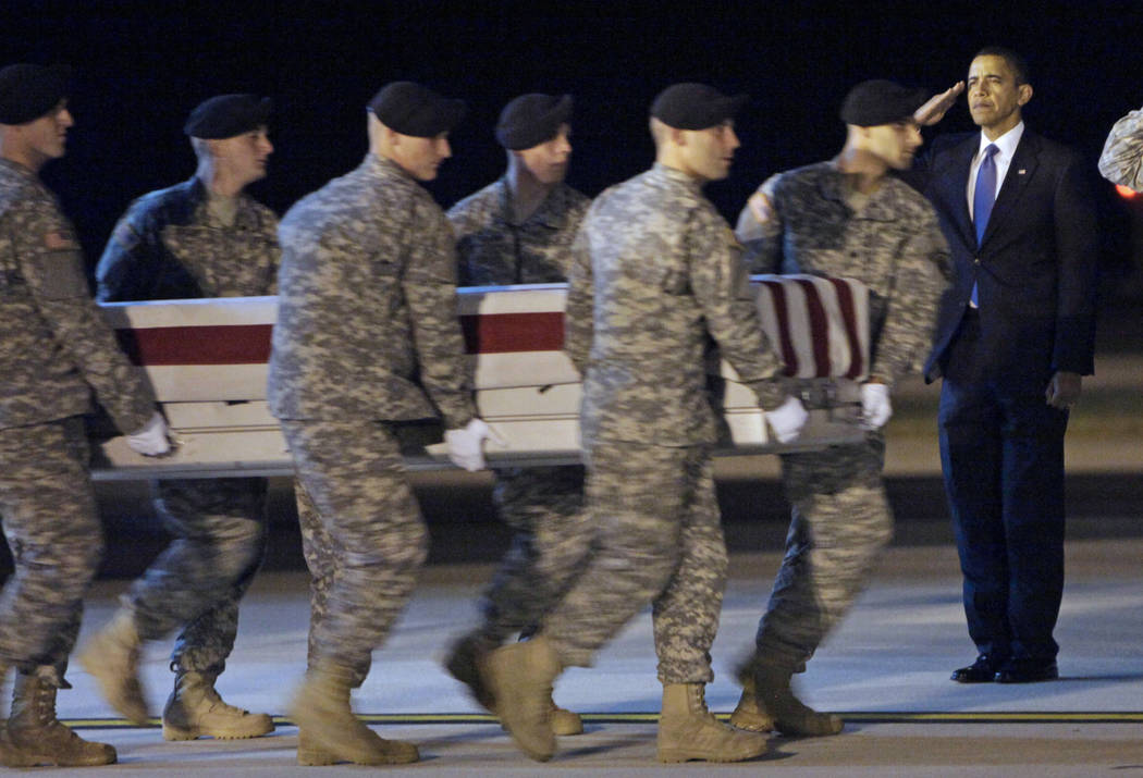 In this Oct. 29, 2009, file photo President Barack Obama, right, salutes as an Army carry team carries the transfer case containing the remains of Sgt. Dale R. Griffin of Terre Haute, Ind., during ...