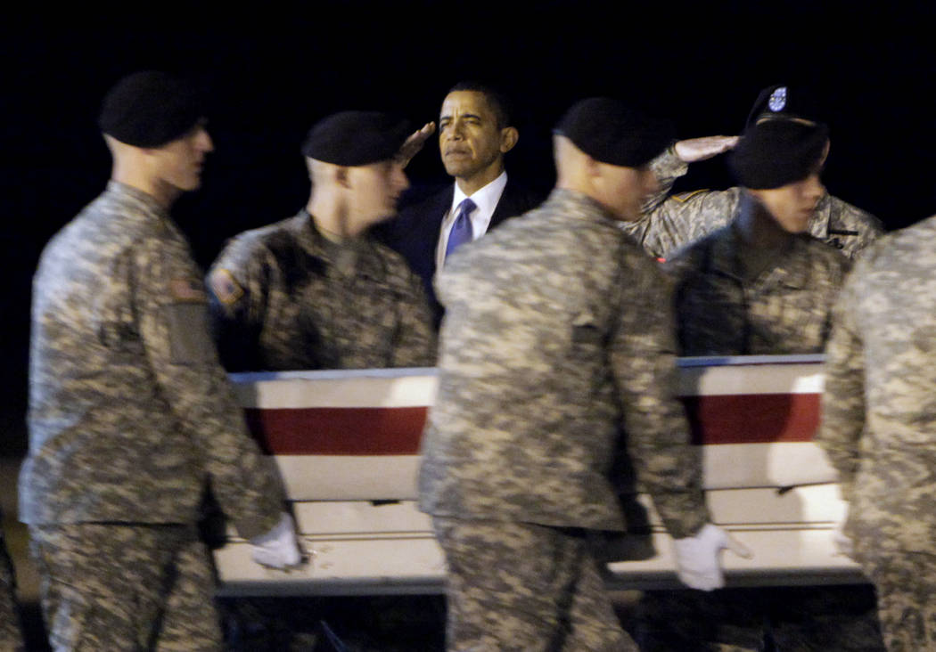 FILE- In this Oct. 29, 2009, file photo, President Barack Obama, center, salutes as an Army carry team carries the transfer case containing the remains of Sgt. Dale R. Griffin of Terre Haute, Ind. ...