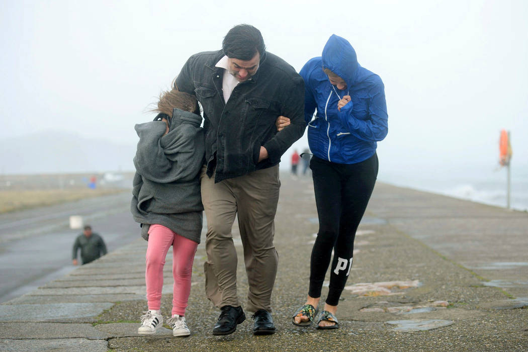 A family walks along a seawall during storm Ophelia on East Pier in Howth, Dublin, Ireland, as the remnants of Hurricane Ophelia batter Ireland and the United Kingdom with gusts of up to 80mph, Mo ...