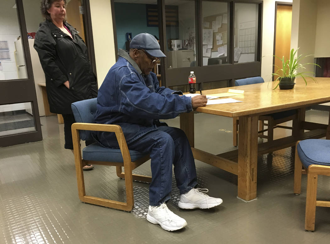 Former football legend O.J. Simpson signs documents at the Lovelock Correctional Center, Saturday, Sept. 30, 2017, in Lovelock, Nev. Simpson was released from the Lovelock Correctional Center in n ...