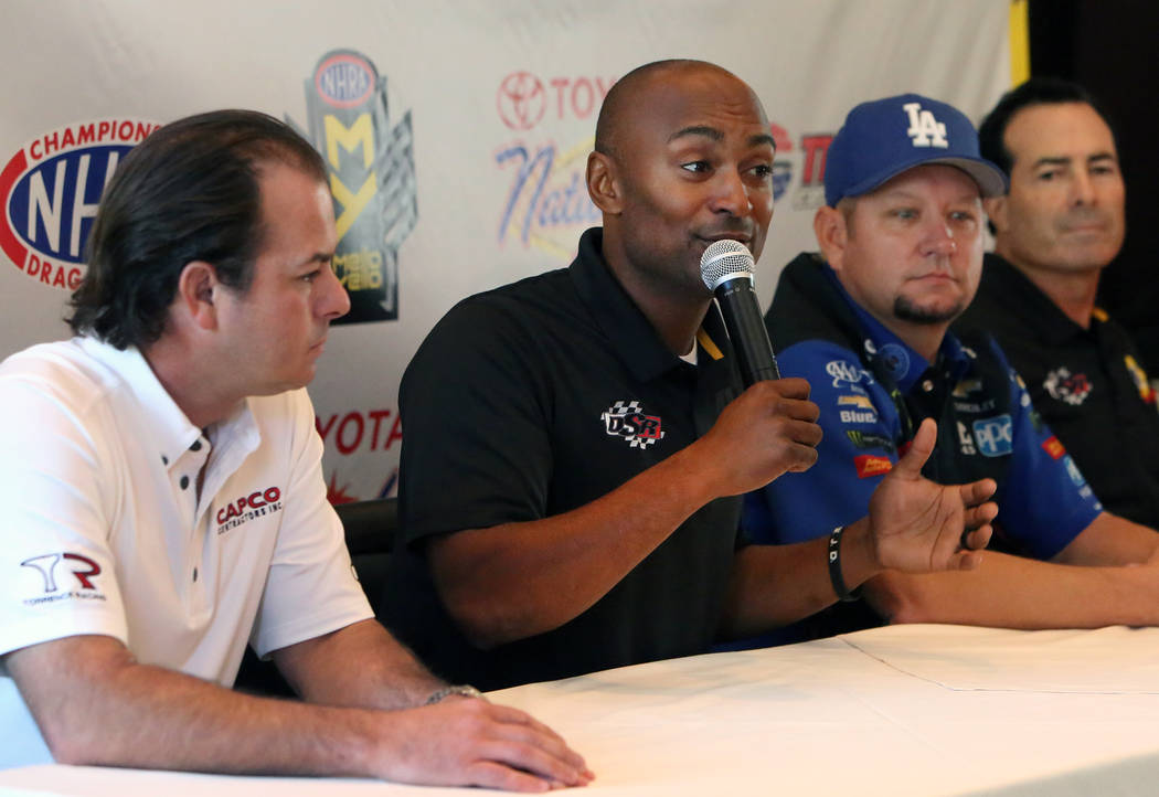Antron Brown, center, driver of the Match Tools / U.S. Army dragster, speaks as Steve Torrence, left, of the Capco Contractors / Torrence Racing dragster, and Robert Hight, second right, of the Au ...