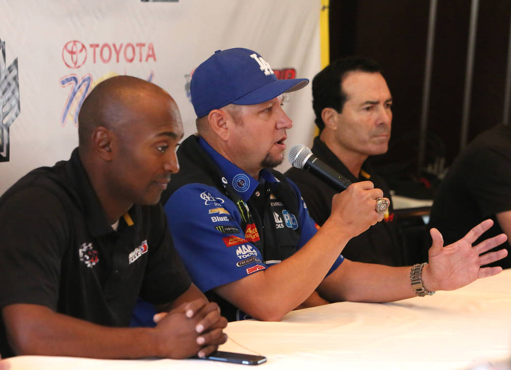 Robert Hight, center, driver of the Auto Club of Souther California Chevy Camaro Funny Car, speaks as Antron Brown, left, of the Match Tools / U.S. Army dragster, and Ron Capps of the NAPA Auto Pa ...