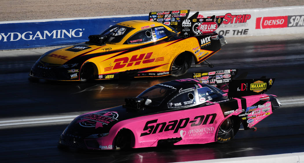 NHRA Funny Car drivers Cruz Pedregon, bottom, and J.R. Todd race during the first round of qualifying for the Mello Yello NHRA Toyota Nationals at The Strip at Las Vegas Motor Speedway Friday Octo ...