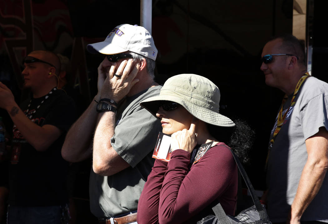 Jim Duffy and his wife Aixa hold their ears as Funny Car racer Doug Kalitta's car is worked on during the second round of qualifying for the Mello Yello NHRA Toyota Nationals event at Las Vegas Mo ...