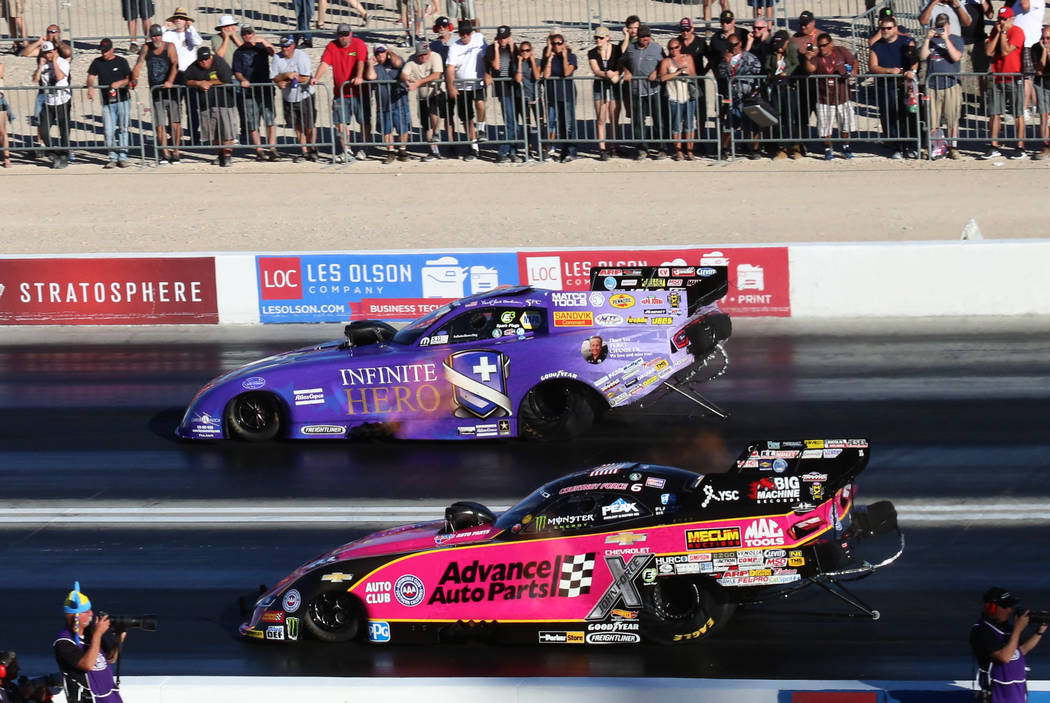 NHRA Funny Car drivers Courtney Force, left, and Jack Beckman race during the third round of qualifying race for the Mello Yello NHRA Toyota Nationals at The Strip at Las Vegas Motor Speedway on S ...