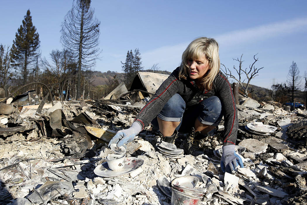 Debbie Wolfe stacks some china to take with her, that once belonged to her grandmother, found in the burned ruins of her home, Tuesday, Oct. 17, 2017, in Santa Rosa, Calif. A massive deadly wildfi ...