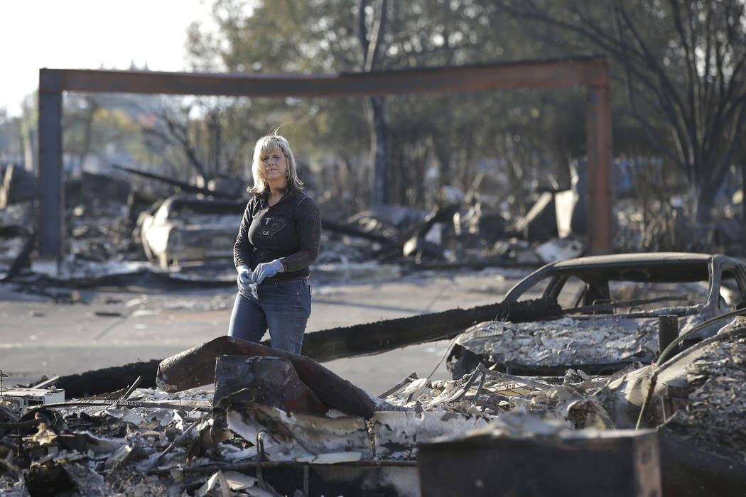 Debbie Wolfe looks over the burned ruins of her home of 30 years Tuesday, Oct. 17, 2017, in Santa Rosa, Calif. A massive deadly wildfire swept through the area last week destroying thousands of ho ...