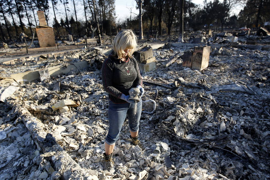 Debbie Wolfe dumps ashes from a pot she found in the burned ruins of her home Tuesday, Oct. 17, 2017, in Santa Rosa, Calif. A massive deadly wildfire swept through the area last week destroying th ...