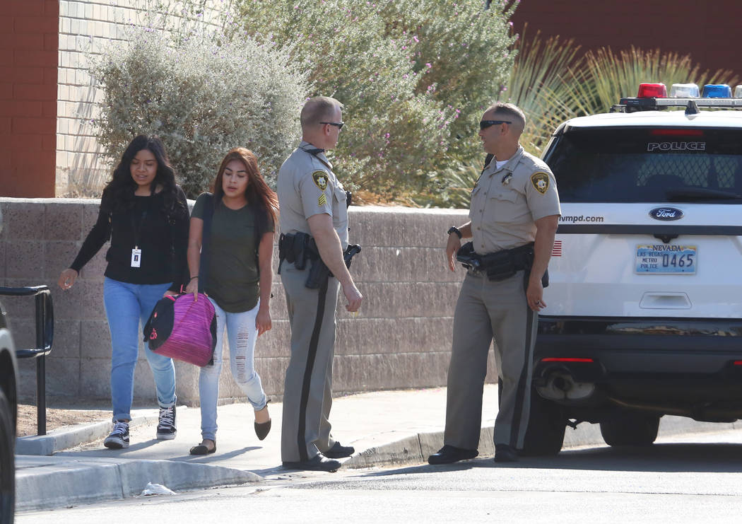Students at Clark High School walk past Las Vegas police officers at their school Monday, Oct. 16, 2017. A 16-year-old student was taken to University Medical Center after she was stabbed by anoth ...