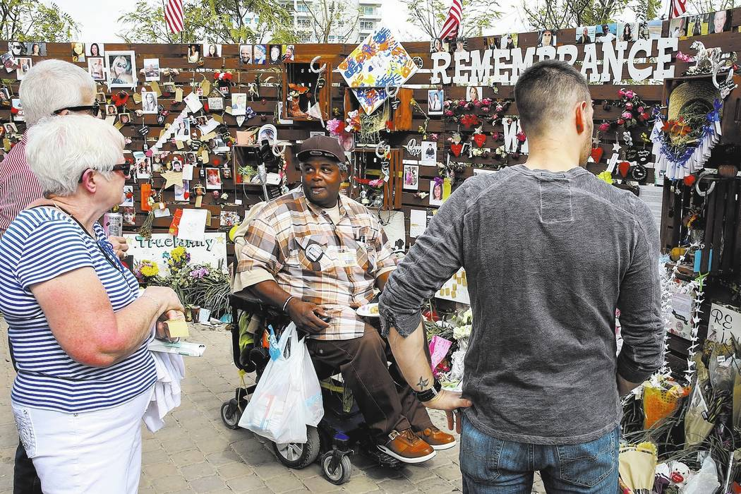 Andre King, center, talks to Shirley Weiskirchen, left, and her husband James, both from Omaha, Nbe., at the healing garden Wednesday, Oct. 18, 2017, in Las Vegas. King has been spending 8-10 hour ...