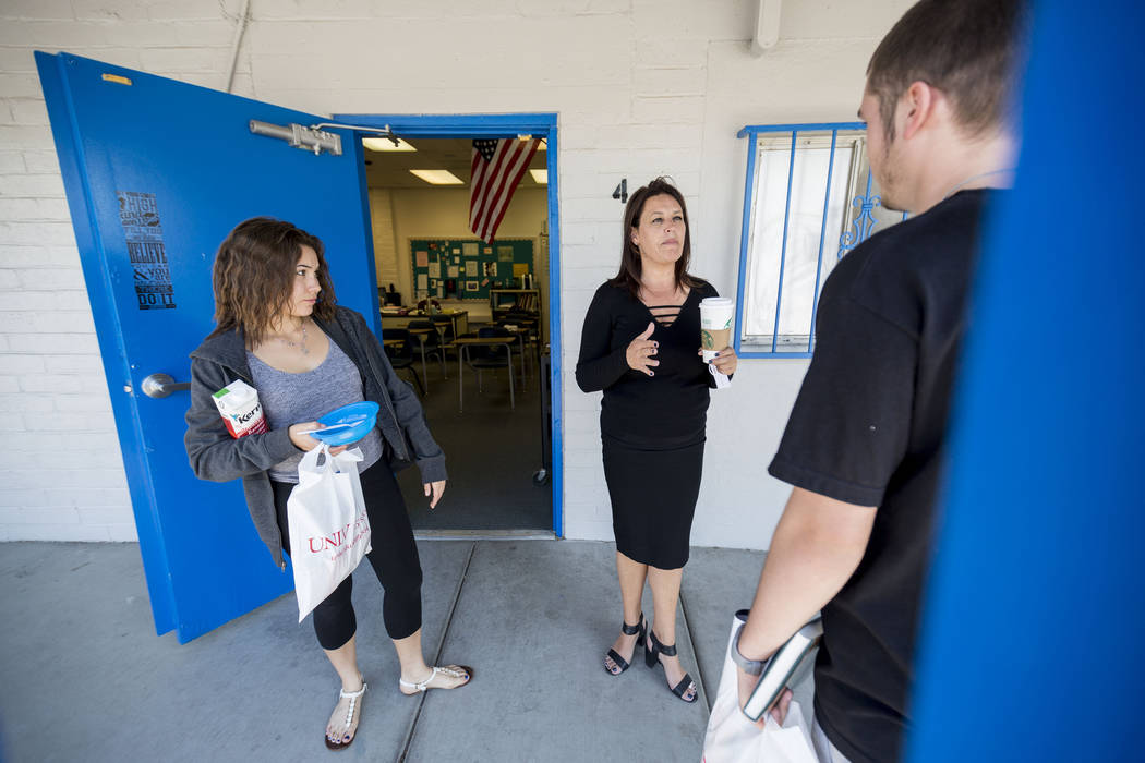 Mission High School student Laura Johnson, 17, left,  principal Barbara Collins, center, speaks with Dylan Bronder, 19, before class begins at Mission High School in Las Vegas, Thursday, Oct. 19,  ...
