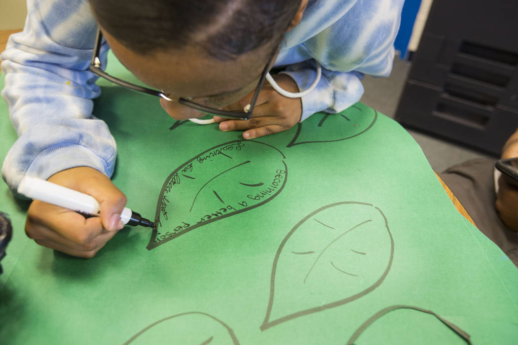 Mission High School student Valacini Dorn, 17, writes how she wants to grow on a paper leaf in the counselors office in Las Vegas, Thursday, Oct. 19, 2017. Mission High School is the district&#x57 ...
