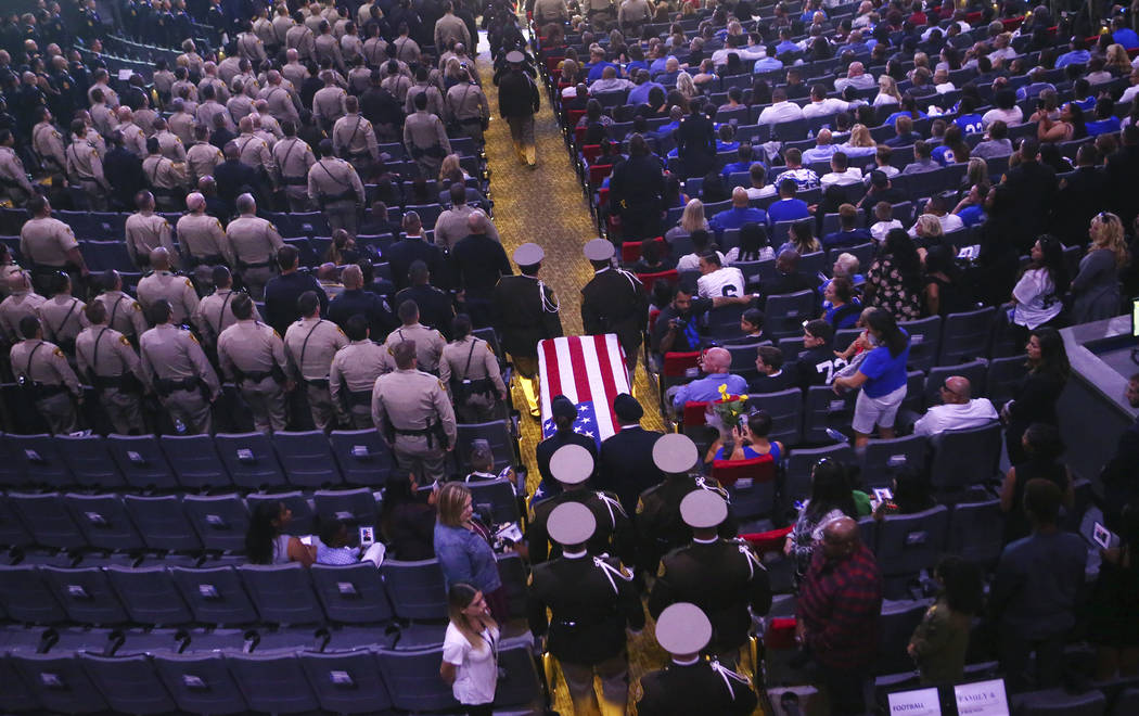 Pallbearers guide in the casket of Las Vegas police officer Charleston Hartfield during his funeral, Friday, Oct. 20, 2017, in Henderson, Nev. Hartfield was killed by a gunman shooting from a hote ...