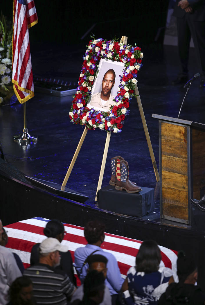 Boots and a picture of Las Vegas police officer Charleston Hartfield are on display at his funeral, Friday, Oct. 20, 2017, in Henderson, Nev. Hartfield was killed by a gunman shooting from a hotel ...