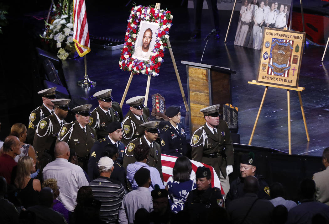Pallbearers move the casket of Las Vegas police officer Charleston Hartfield, Friday, Oct. 20, 2017, in Henderson, Nev. Hartfield was killed by a gunman shooting from a hotel into a crowded outdoo ...